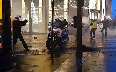 Screen capture from  video shows a police biker, left, drawing his firearm as he and other police bikers are assaulted by protesters on the Champs-Elysees in Paris, December 22, 2018. (LINE PRESS/AFP)
