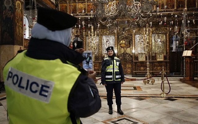 Palestinian female police officers take pictures inside the Church of the Nativity in the biblical West Bank city of Bethlehem, on December 24, 2018. (HAZEM BADER/AFP)