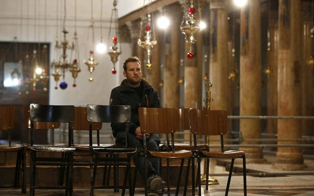 A Christian worshipper sits inside the Church of the Nativity in the biblical West Bank city of Bethlehem, on December 24,2018. (HAZEM BADER/AFP)