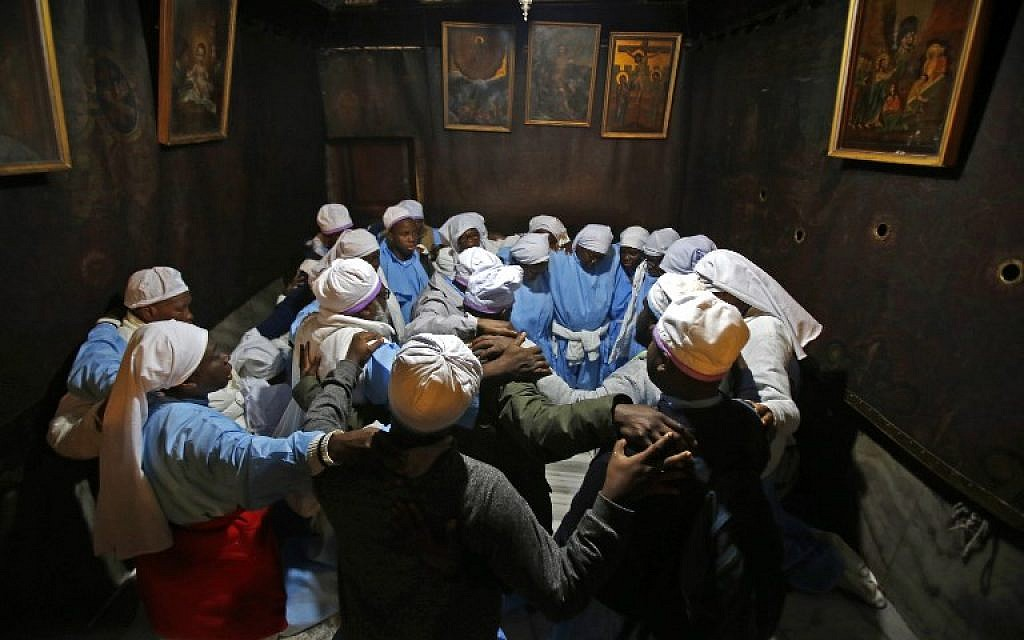 Nigerian pilgrims pray inside the Grotto, believed to be the exact spot where Jesus Christ was born, at the Church of the Nativity in the biblical West Bank city of Bethlehem, on the eve of the Christmas celebration, December 24, 2018. (Musa Al SHAER/AFP)