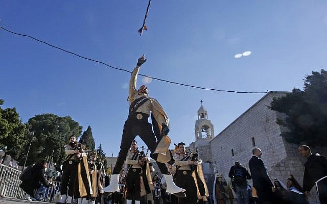 Palestinian bagpipers perform on Manger square in front of the Church of the Nativity in the biblical West Bank city of Bethlehem, on December 24, 2018. (Musa Al SHAER/AFP)