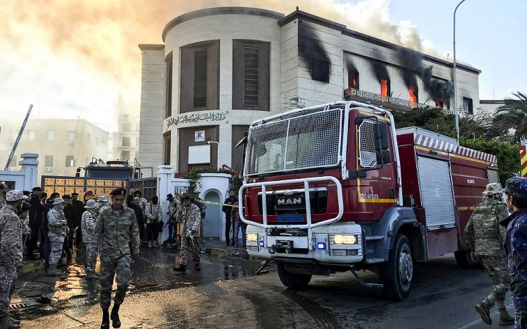 A picture taken on December 25, 2018, shows a firetruck and security officers at the scene of an attack outside the Libyan foreign ministry headquarters in the capital Tripoli. (Mahmud Turkia/AFP)