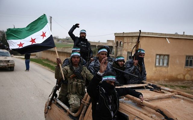 Turkish-backed Syrian fighters raise the opposition flag as they arrive in the border rebel-held town of Qirata after leaving their barracks in the town of Jarabulus on their way to the northern town of Manbij, on December 25, 2018, (Nazeer AL-KHATIB / AFP)