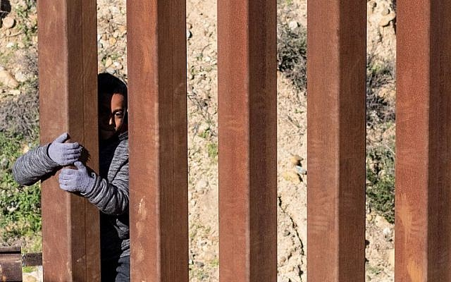 Mexican migrant child Kevin Andres, from Guerrero state, crosses the US-Mexico border fence from Tijuana to San Diego County in the US, as seen from Tijuana, Baja California state, Mexico, on December 28, 2018. (Guillermo Arias / AFP)