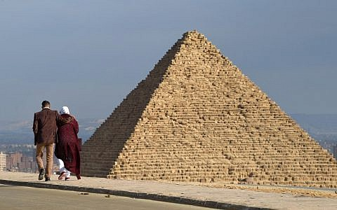 A couple walk along a road at the Giza pyramids necropolis on the southwestern outskirts of the Egyptian capital Cairo on December 29, 2018, with the pyramid of Menkaure (or Menkheres) seen in the background. (MOHAMED EL-SHAHED / AFP)