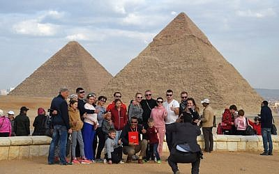 Tourists pose for a group picture at the Giza pyramids necropolis on the southwestern outskirts of the Egyptian capital Cairo on December 29, 2018, with the pyramids of Khafre (or Chephren, R) and Khufu (or Cheops, L) seen in the background. (MOHAMED EL-SHAHED / AFP)