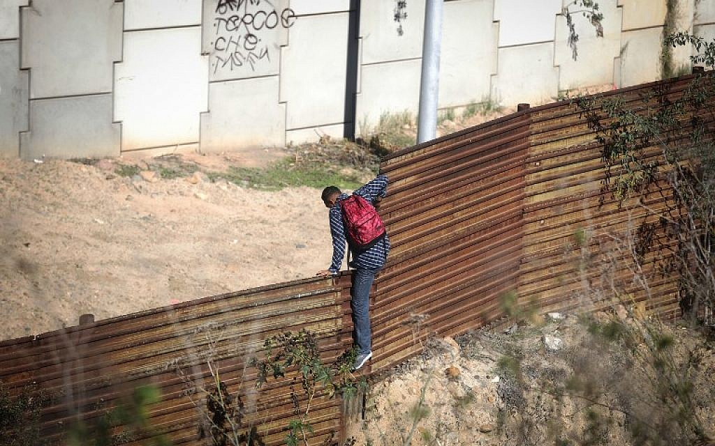 A migrant crosses the US-Mexico border fence before turning himself in to US Border Patrol in Tijuana, Mexico, on December 16, 2018. (Mario Tama/Getty Images/AFP)
