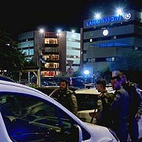 Police at the scene of a shooting in Lod, outside police's national fraud unit (Hadashot TV news screenshot)