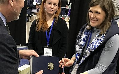 A new facsimile of the 14th-century Sarajevo Hagaddah was on display, and for sale, by the National Museum of Bosnia and Herzegovina in the exhibit hall at the Association of Jewish Studies convention, held in Boston, Mass., Dec. 16-18, 2018. (Penny Schwartz/JTA)