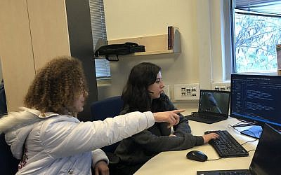 Ayelet Ganot, left, and Roni Ashkenazi, participants in the Carmel 6000 national service program, work on an app intended to help autistic children cope with change. (Sam Sokol/JTA)