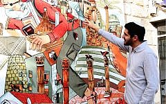 """Poet and playwright Roie Ravitzky, creator of Jerusalem's """"Street Talk"""" art series, in front of a mural on Gaza street in Jerusalem. (Shmuel Bar-Am)"""