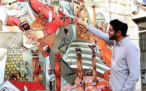 "Poet and playwright Roie Ravitzky, creator of Jerusalem's ""Street Talk"" art series, in front of a mural on Gaza street in Jerusalem. (Shmuel Bar-Am)"