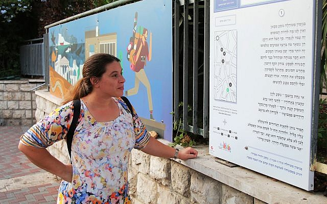 """A passerby reads part of the """"Street Talk"""" exhibition in Jerusalem. (Shmuel Bar-Am)"""