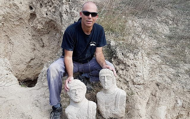 Nir Distelfeld, Israel Antiquities Authority Theft Prevention Unit inspector, with the pair of limestone funerary busts, which were discerned by a hiker after early December heavy rains in the Beit She'an region. (Eitan Klein, Israel Antiquities Authority)