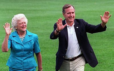 In this Aug. 24, 1992, file photo, President George H.W. Bush and first lady Barbara Bush walk with their dog Millie across the South Lawn as they return to the White House (AP Photo/Scott Applewhite, File)