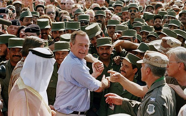 In this Nov. 22, 1990 file photo, President George H.W. Bush is greeted by Saudi troops and others as he arrives in Dhahran, Saudi Arabia, for a Thanksgiving visit (AP Photo/J. Scott Applewhite, File)