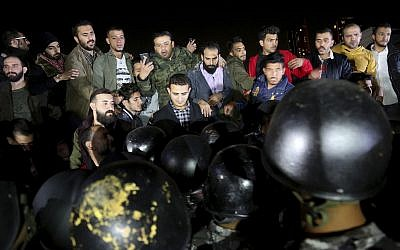 Jordanian policemen surround protesters to prevent them from reaching the nearby cabinet headquarters, in the capital Amman, Friday, Nov. 30, 2018. (AP/Raad Adayleh)