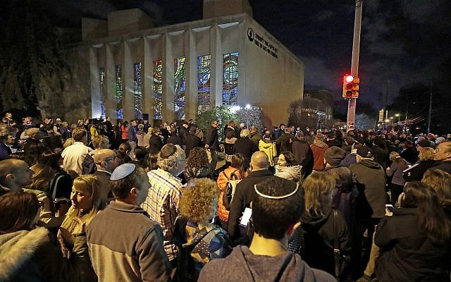 Rabbi Jeffrey Myers leads a gathering in Hanukkah songs after lighting a menorah outside the Tree of Life Synagogue on the first night of Hanukkah, Sunday, Dec. 2, 2018 in the Squirrel Hill neighborhood of Pittsburgh. A gunman shot and killed 11 people while they worshipped Saturday, Oct. 27, 2018 at the temple. (AP Photo/Gene J. Puskar)