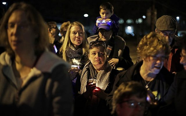 People watch as a menorah is lighted outside the Tree of Life Synagogue on the first night of Hanukkah, December 2, 2018 in the Squirrel Hill neighborhood of Pittsburgh. A gunman shot and killed 11 people while they worshiped Saturday, October 27, 2018 at the temple. (AP Photo/Gene J. Puskar)