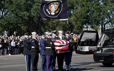 The flag-draped casket of former US President George H.W. Bush is carried by a joint services military honor guard to Special Air Mission 41 at Ellington Field during a departure ceremony on December 3, 2018, in Houston. (AP Photo/David J. Phillip, Pool)