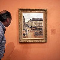 "This May 12, 2005, file photo shows an unidentified visitor viewing the Impressionist painting called ""Rue St.-Honore, Apres-Midi, Effet de Pluie"" painted in 1897 by Camille Pissarro, on display in the Thyssen-Bornemisza Museum in Madrid. (AP Photo/Mariana Eliano, File)"