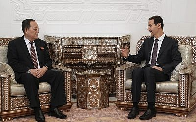 In this photo released by the Syrian official news agency SANA, Syrian President Bashar Assad, right, meets with North Korea's Foreign Minister Ri Yong Ho in Damascus, Syria, Tuesday, Dec. 4, 2018. (SANA via AP)