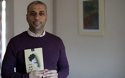 "In this December 4, 2018, photo, journalist and author Shady Lewis Botros poses with a copy of his book, ""Ways of the Lord,"" in London. (AP Photo/Matt Dunham)"