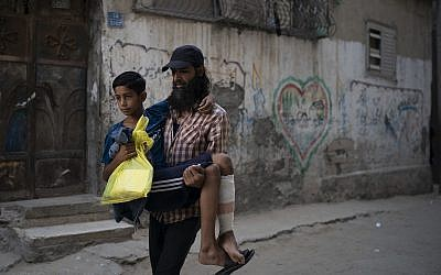 In this September 16, 2018, photo, Raed Abu Khader, right, carries his 12-year-old son Mohammed as they return from the hospital in Gaza City. Mohammed was shot in the leg at one of the demonstrations on Gaza's border with Israel. (AP Photo/Felipe Dana)