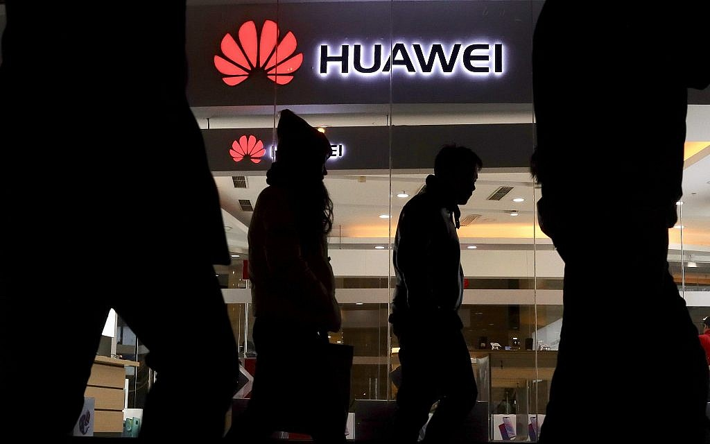 Pedestrians walk past a Huawei retail shop in Beijing Thursday, Dec. 6, 2018. China on Thursday demanded Canada release a Huawei Technologies executive who was arrested in a case that adds to technology tensions with Washington and threatens to complicate trade talks. (AP Photo/Ng Han Guan)