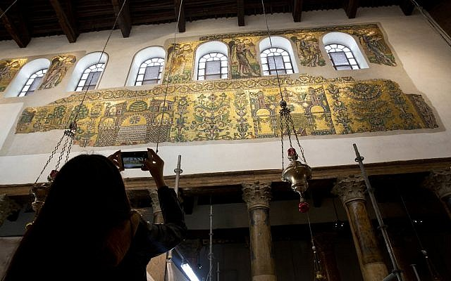 A visitor photographs a renovated part of a fresco inside the Church of the Nativity in the West Bank City of Bethlehem, December 6, 2018. (Majdi Mohammed/AP)