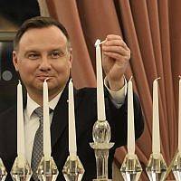 Polish President Andrzej Duda lights the menorah celebrating Hanukkah, the Jewish festival of lights, at the presidential palace in Warsaw, Poland, Dec. 9, 2018. (AP Photo/Alik Keplicz)