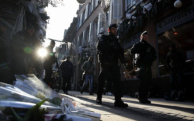 French police officers patrol in Strasbourg, France, in front of flowers commemorating the victims of a deadly December 11, 2018, terror attack, on Thursday, December 13, 2018. (AP Photo/Christophe Ena)