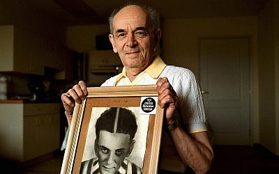 In this 2001 photo, Alter Wiener, born in 1926, holds up a photo of himself taken in July 1945, two months after he was liberated from a Nazi death camp, in his apartment in Aloha, Oregon. (Benjamin Brink/The Oregonian via AP)