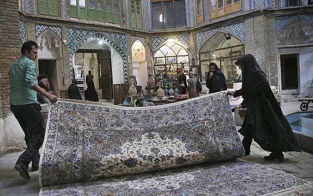 In this photo from December 10, 2018, two carpet weavers open their hand-woven carpet at the grand bazaar in Kashan, Iran. (AP Photo/Vahid Salemi)