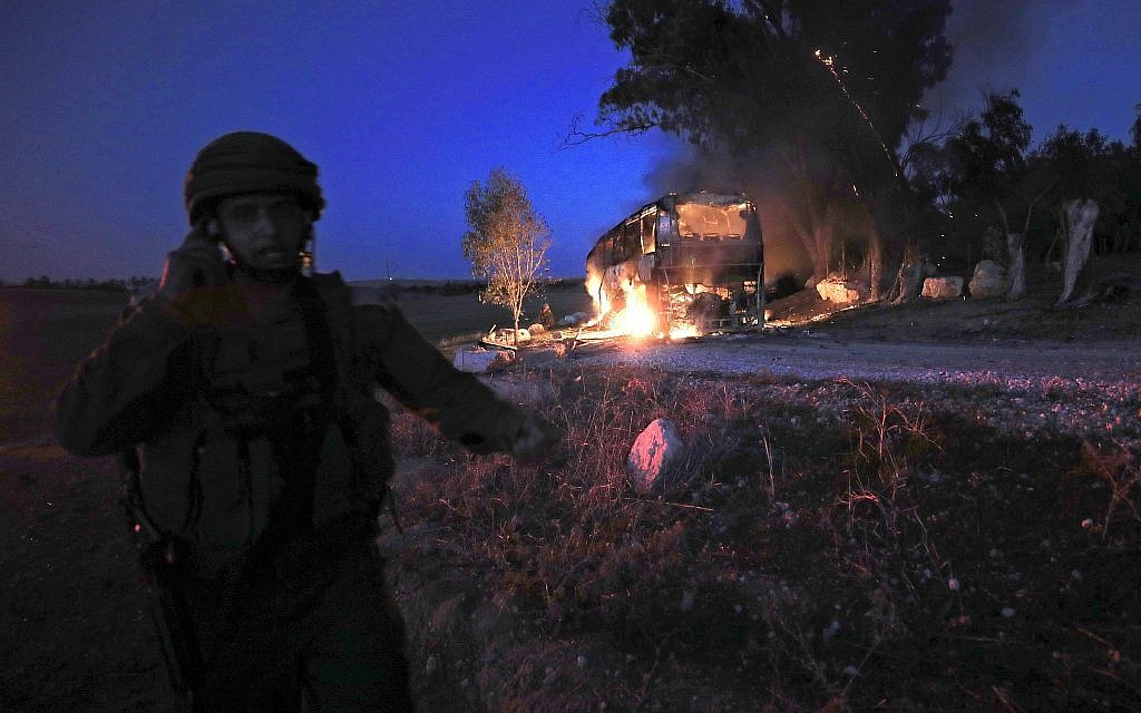 An Israeli soldier stands near a burning bus after it was hit by an anti-tank missilel fired from Gaza Strip near the Israel-Gaza border, Monday, November 12, 2018. (Tsafrir Abayov/AP)