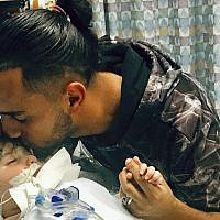 This recent but undated photo, released Dec. 17, 2018, by the Council on American-Islamic Relations in Sacramento, Calif., shows Ali Hassan kissing his dying 2-year-old son Abdullah in a Sacramento hospital (Council on American-Islamic Relations via AP)