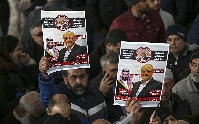 In this photo from November 16, 2018, members of Arab-Turkish Media Association and friends of Washington Post columnist Jamal Khashoggi hold posters showing images of Saudi Crown Prince Muhammed bin Salman and of Khashoggi, as they attend funeral prayers in absentia for him following his killing the previous month in the Saudi Arabia consulate, in Istanbul. (AP Photo/Emrah Gurel, File)