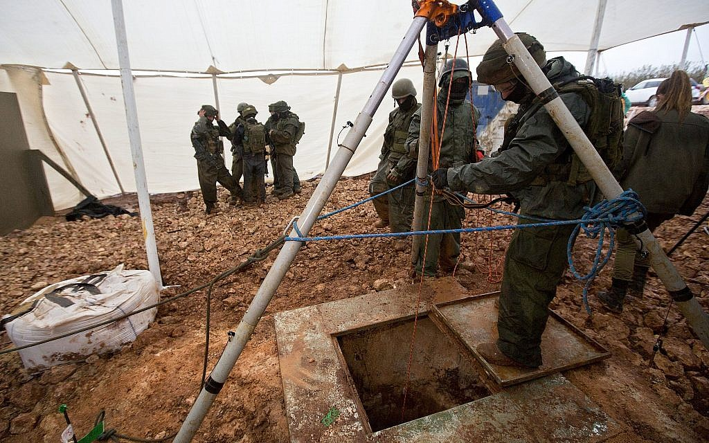 Israeli soldiers stand around the opening of a hole that leads to a tunnel that the army says was dug by the Hezbollah terror group across the Israel-Lebanon border, near Metula, on December 19, 2018. (AP Photo/Sebastian Scheiner)