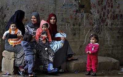In this Tuesday, December 18, 2018, photo, Syrian refugee women hold their children as they sit in Ouzai refugee compound, in the southern port city of Sidon, Lebanon. (AP Photo/Bilal Hussein)