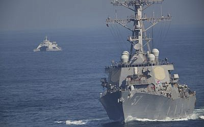 The USS Mitscher, part of a strike group led by the USS John C. Stennis aircraft carrier, sails as an Iranian Revolutionary Guard vessel shadows it on December 21, 2018. (AP Photo/Jon Gambrell)