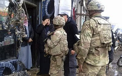 This photo released on the Facebook page of the Military Council of Manbij City, shows US troops based around the Syrian town of Manbij speaking with residents, in northern Syria on December 23, 2018. (The Military Council of Manbij City via AP)