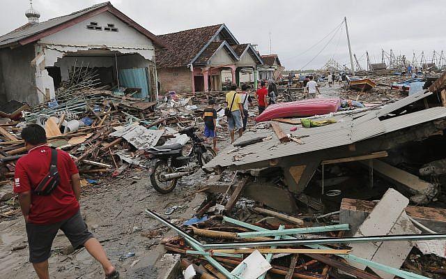 People inspect the damage at a tsunami-ravaged village in Sumur, Indonesia, December 25, 2018. (Tatan Syuflana/AP)