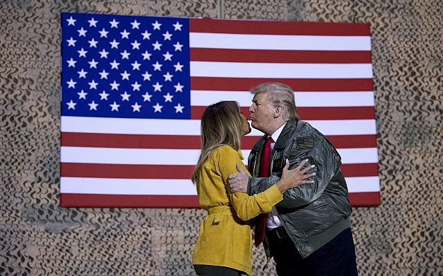 US President Donald Trump kisses first lady Melania Trump during a hanger rally at Al Asad Air Base, Iraq, on December 26, 2018. (AP Photo/Andrew Harnik)
