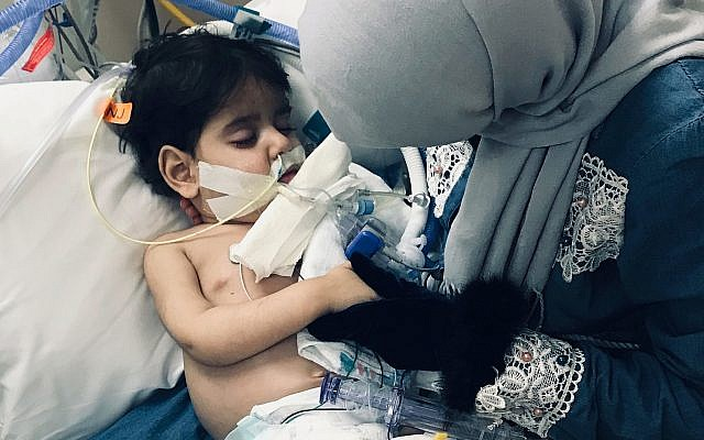 In this December 2018 photo released by the Council on American Islamic Relations, Sacramento Valley, Shaima Swileh, of Yemen, holds her dying 2-year old son Abdullah Hassan at UCSF Benioff Children's Hospital in Oakland, California, USA. (Council on American Islamic Relations, Sacramento Valley via AP)