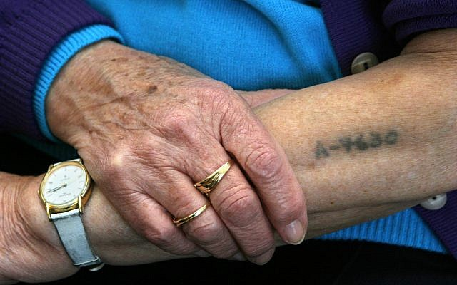 Holocaust survivor Bracha Ghilai, 75, shows her tattooed arm at her house in Holon near Tel Aviv, January 23, 2005. (AP/Ariel Schalit)