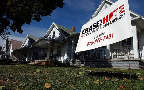 "An ""Erase the Hate"" sign stands in the front lawn of a home, Monday, Oct. 17, 2005, in Toledo, Ohio, near where a mob looted and burned a neighborhood bar, smashed the windows of a gas station, and hurling rocks and bottles at police on Saturday. (AP/J.D. Pooley)"