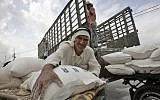 A Palestinian man loads flour bags onto a donkey cart outside the United Nations World Food Programme distribution center in the Rafah refugee camp, southern Gaza Strip,Nov. 7, 2007 (AP Photo/Khalil Hamra)