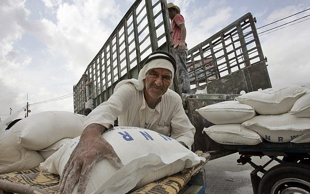 A Palestinian man loads flour bags onto a donkey cart outside the United Nations World Food Program distribution center in the Rafah refugee camp, southern Gaza Strip,Nov. 7, 2007 (AP Photo/Khalil Hamra)