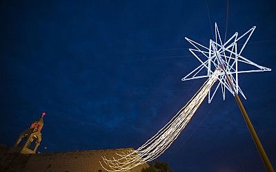 A Christmas star is seen in front of the Church of Nativity, believed to be the birthplace of Jesus Christ, in the West Bank town of Bethlehem, on Dec. 21, 2008. (AP Photo/Bernat Armangue)