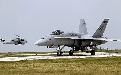 "Illustrative: A Marine F-18 ""Super Hornet"" taxies as a AH-1 Cobra helicopter lands at Burke Lakefront Airport in Cleveland Saturday, June 16, 2012 as part of Marine Week in the city. (AP Photo/Mark Duncan)"